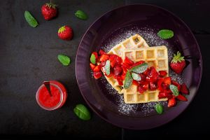 plates food waffles strawberries fruit mint leaves sugar  still life