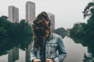 reflection women outdoors brunette hair in face lake long hair windy jean jacket model depth of field women