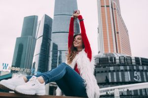 roma roma arms up sneakers jeans necklace building happy brunette red tops sky women model depth of field fila sitting