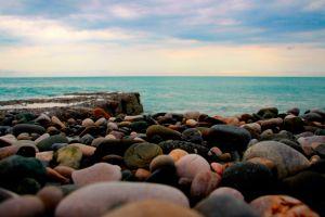 sky coast stones clouds horizon