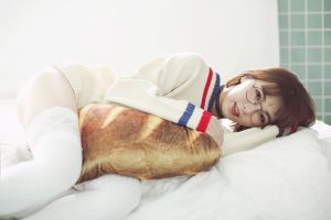 smiling model pillow hug women indoors sweater asian stockings indoors fake glasses portrait in bed lying on side necklace white stockings brunette