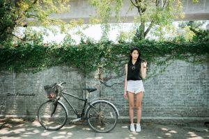 standing bicycle wall black tops skinny urban women asian women outdoors black hair jean shorts plants jean shorts sneakers