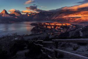 sunset mountains city spain bay fence building nature clouds plants road landscape bridge
