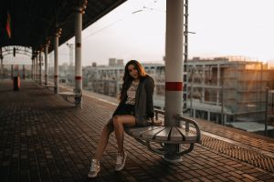 train station tanned women portrait sneakers smiling jean shorts sitting