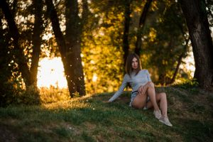 women brunette smiling jean shorts sneakers grass sitting trees