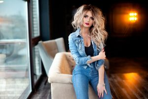 women indoors long hair red nails blonde jeans jeans jacket model sitting looking at viewer depth of field denim portrait necklace carl gia
