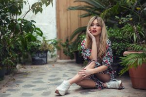 women indoors red lipstick hand on face on the floor open mouth sitting blonde plants