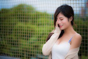 women outdoors depth of field closed eyes hand on face brunette women asian smiling open sweater model