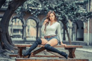 women outdoors depth of field necklace asian portrait knee-high boots trees women model belt looking at viewer jean shorts white tops outdoors sitting