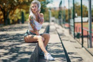 women outdoors jean shorts tattoo white tops brunette sneakers women sitting women with glasses