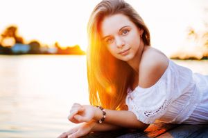 wood bare shoulders portrait model dress brunette smiling lying on front depth of field lens flare outdoors women outdoors sunset women looking at viewer
