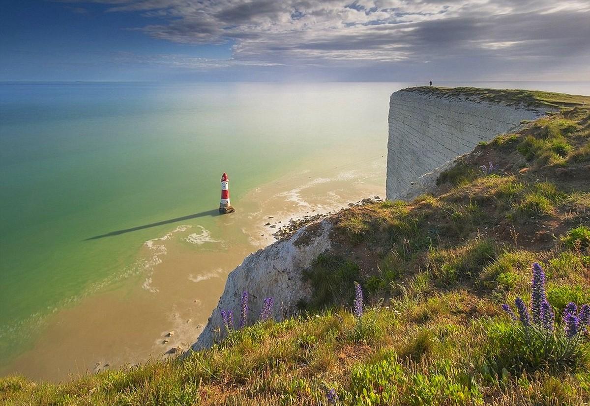 clouds horizon sea beach grass cliff nature wildflowers lighthouse landscape