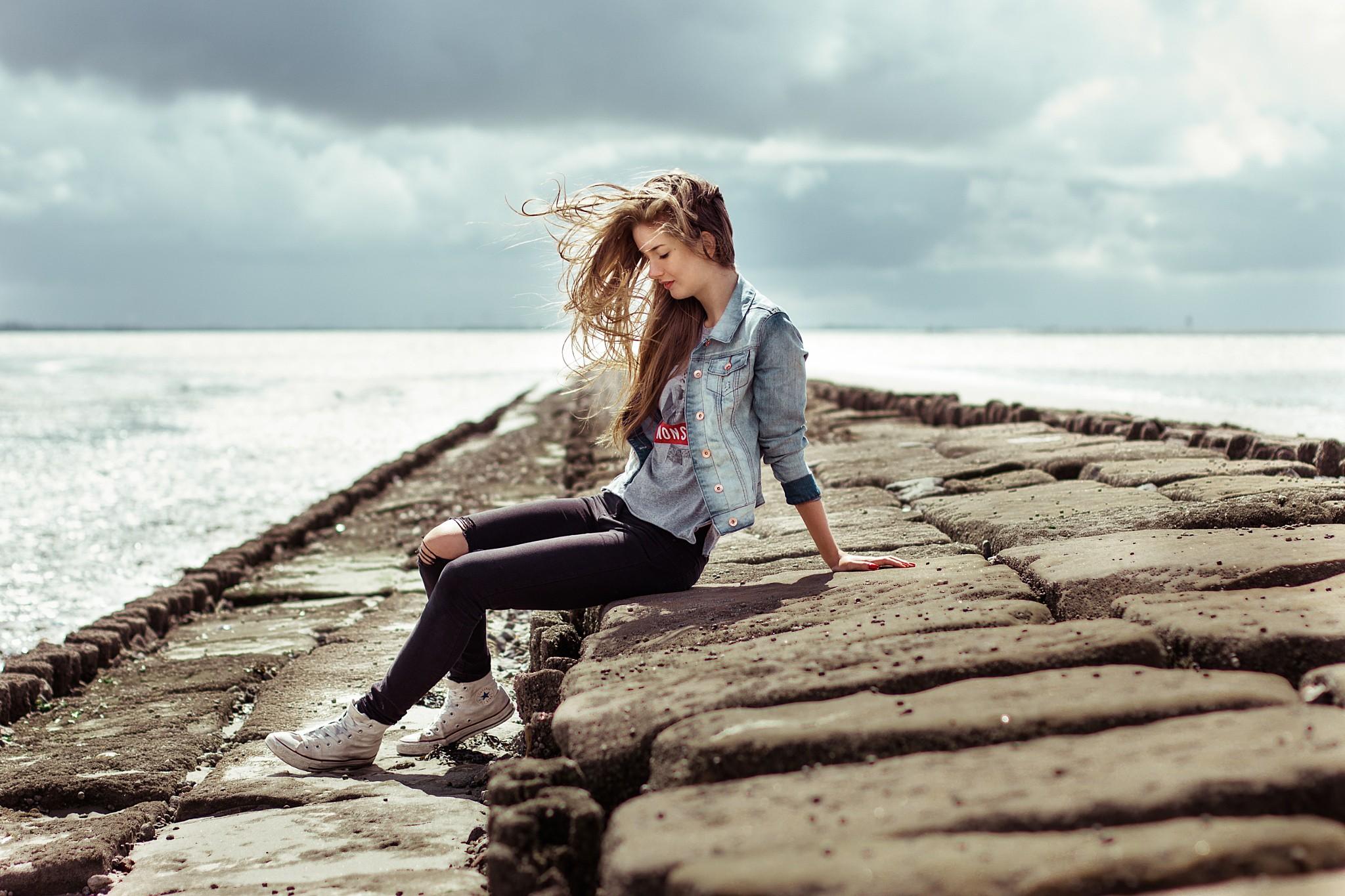 jeans closed eyes torn jeans sitting blonde sneakers women sea sneakers