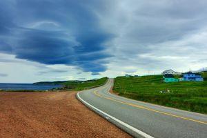 asphalt sea gray blue landscape nature gravel green sky road grass clouds hills horizon