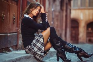 auburn hair looking away street hands in hair long hair plaid skirt skirt depth of field women outdoors knee-high boots women sitting