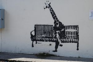 banksy shadow artwork sitting street art bench animals graffiti giraffes legs wall