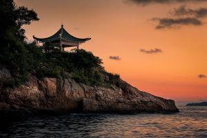 coast sea pagoda shrubs rock trees sunset landscape nature