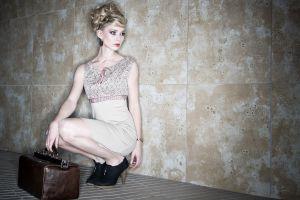 deborah frey blonde model squatting suitcase women looking away beige