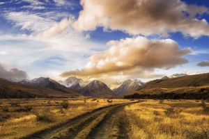 dirt road landscape nature new zealand mountains sunset clouds dry grass shrubs panoramas snowy peak