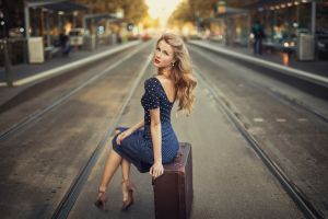 earring long hair model polka dots sitting depth of field rail yard high heels stiletto women outdoors red lipstick women blonde looking at viewer suitcase