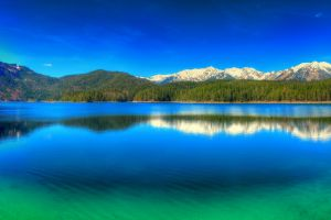 forest snowy peak green reflection sky water landscape germany nature mountains panoramas blue lake