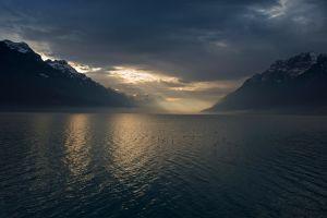 lake nature sun rays dark mountains snowy peak birds atmosphere sunlight switzerland landscape winter mist clouds