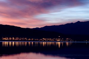 lake sunset mountains water city calm reflection cityscape lights evening