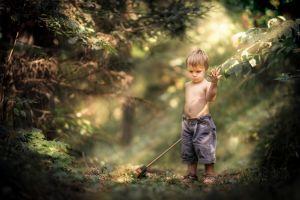 little boy children sun rays nature forest