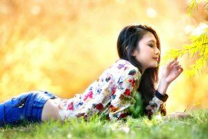 lying on front depth of field grass smiling fall jeans brunette asian flowers long hair korean face nature park women outdoors