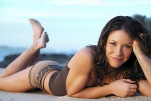 lying on front shorts sand covered women brown tops women on beach smiling actress evangeline lilly feet in the air
