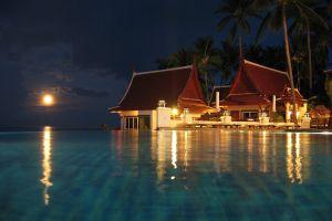 night swimming pool resort palm trees tropical