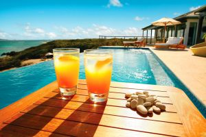orange stones wooden surface drinking glass beach swimming pool sea sunlight coast tropical shadow table pebbles