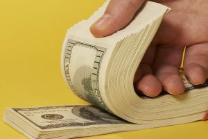 paper numbers yellow background hands money