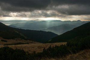 shrubs brown landscape far view clouds dark field hills nature sun rays