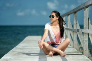sitting asian feet brunette barefoot short shorts dock ponytail legs crossed sea sunglasses women