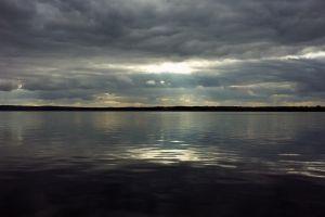 sun rays lake river gray sky water russia clouds