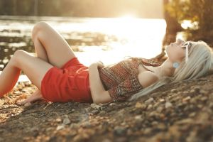 sunglasses painted nails lying on back red clothing blonde women bent legs