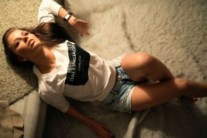 top view women brunette looking into the distance thinking long hair model white sweater jean shorts sitting