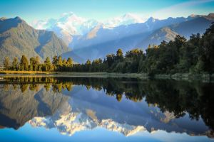trees nature sky forest new zealand landscape water sunlight mountains snowy peak lake mirrored hills reflection