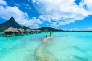water landscape vacation island sea nature turquoise resort palm trees mountains clouds beach bungalow bora bora tropical