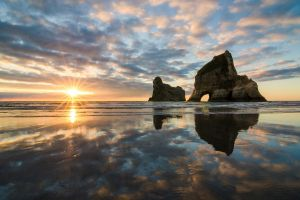 waves clouds nature beach water lens flare rock landscape rock formation coast reflection sunset