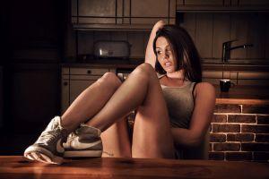 women looking into the distance sitting tank top laurent kacé model brunette sneakers women indoors