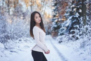 women sweater juicy lips brown eyes model asian winter pine trees forest long hair trees snow brunette nature tight clothing