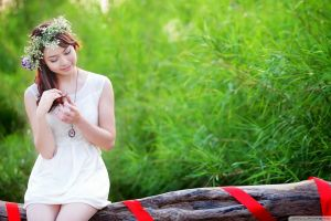 wreaths hands in hair necklace auburn hair asian outdoors women looking away smiling sitting white dress